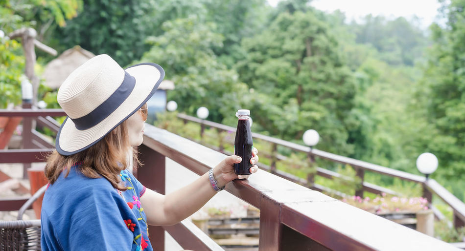 Rear view of woman with hat on railing