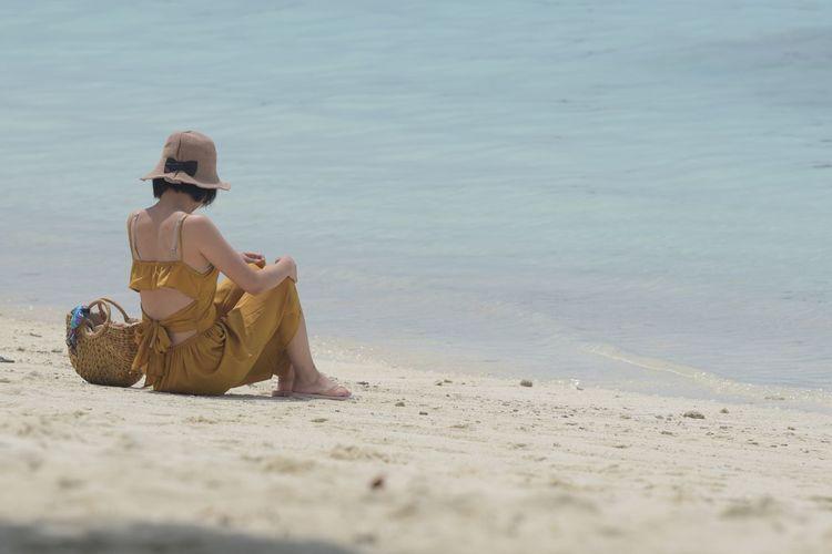 Man sitting on sand at beach