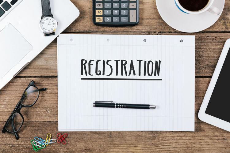 Registration headline on paper note pad Text Close-up Communication Concept Day Desk Headline High Angle View Indoors  No People Office Paper Pen Pencil Registration Stapler Table Technology Text Wireless Technology