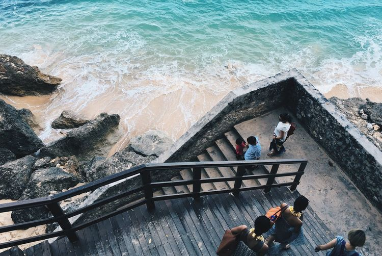 High angle view of people walking on steps by beach