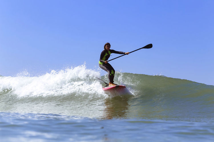 Full length of man surfing in sea against clear sky