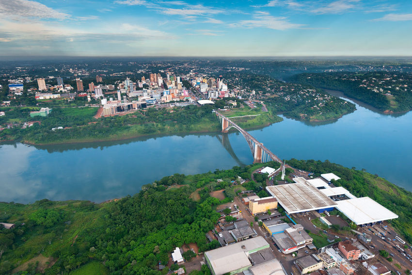 Aerial view of the Paraguayan city of Ciudad del Este and Friendship Bridge, connecting Paraguay and Brazil through the border over the Parana River, with Brazilian customs and immigrations facilities in the foreground. Brazil City Cityscape Ciudad Del Este Paraná River Skyline Aerial View Border Bridge Customs Friendship Bridge Latin American Paraguay River