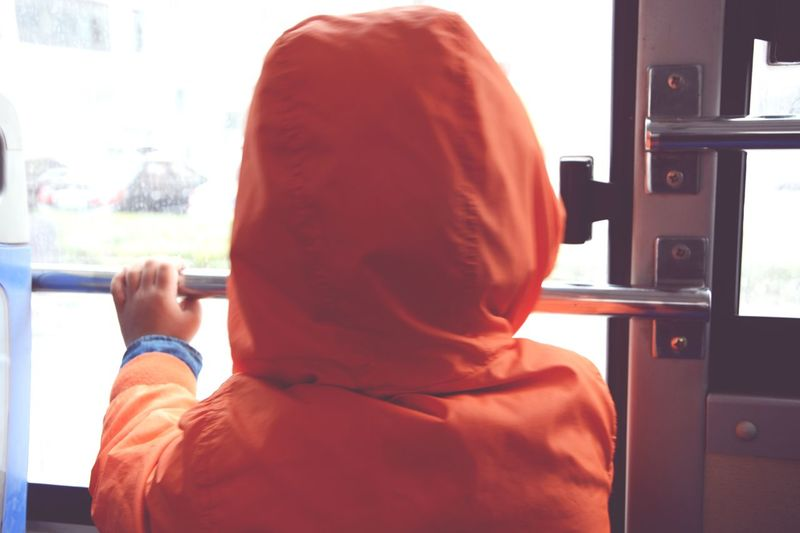 Rear view of kid in orange hooded jacket standing by bus door