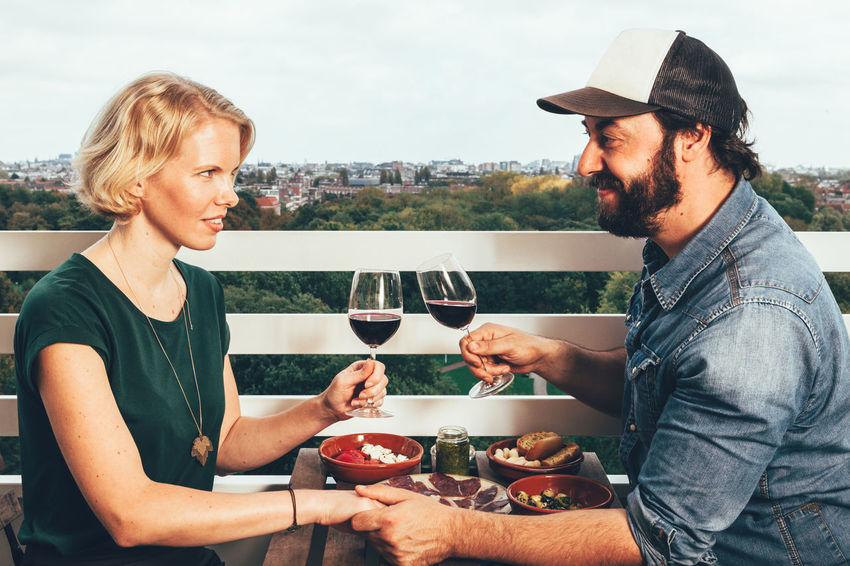 young couple dining on a terrace Couple Toasting Alcohol Bonding Casual Clothing Day Drink Drinking Drinking Glass Food Food And Drink Friendship Happiness Lifestyles Outdoors Real People Red Wine Smiling Togetherness Two People Wine Wineglass Young Adult