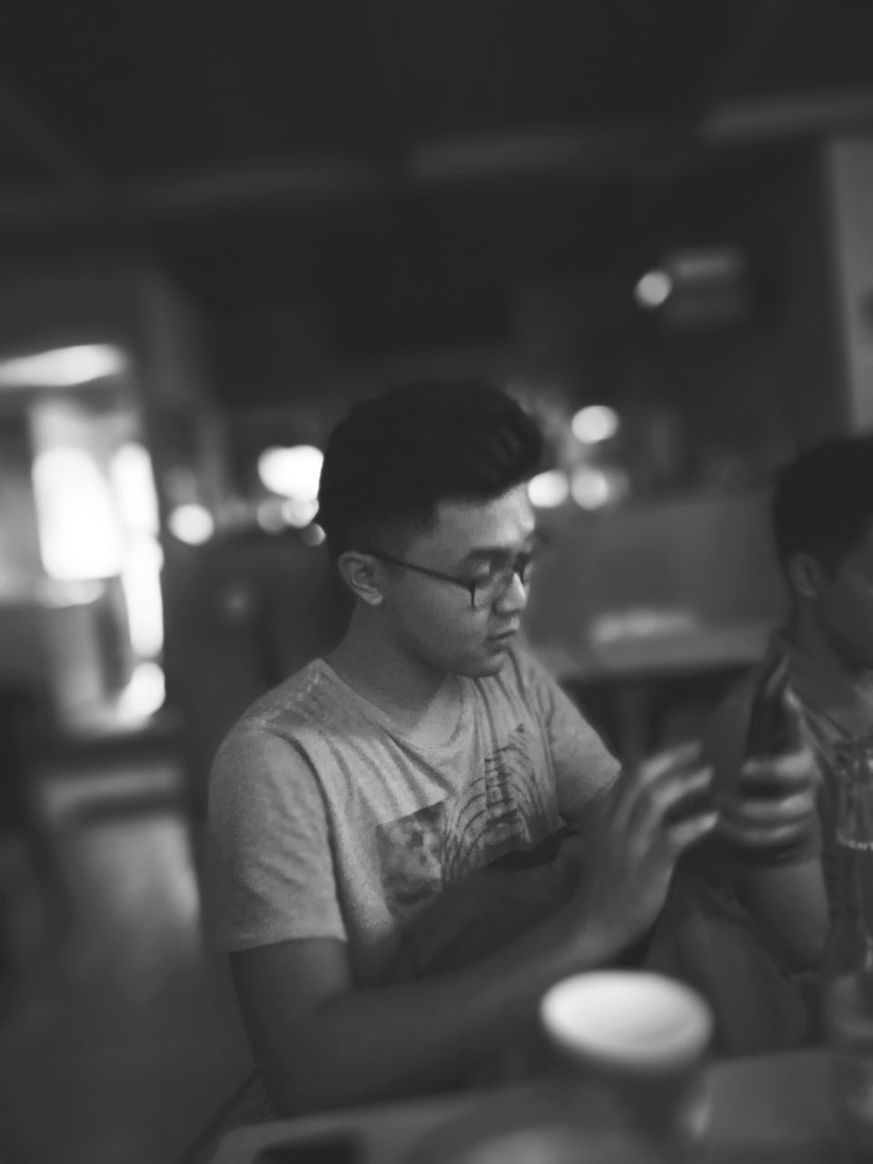 real people, sitting, indoors, one person, focus on foreground, eyeglasses, lifestyles, wireless technology, leisure activity, communication, young adult, illuminated, men, night, young women, human hand, close-up, people