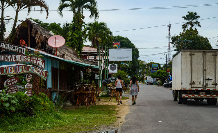 Costa Rica Architecture Building Exterior Built Structure Cahuita Caribbean Day Electricity Pylon Land Vehicle Outdoors People Plant Real People Road Text Town Tree Women