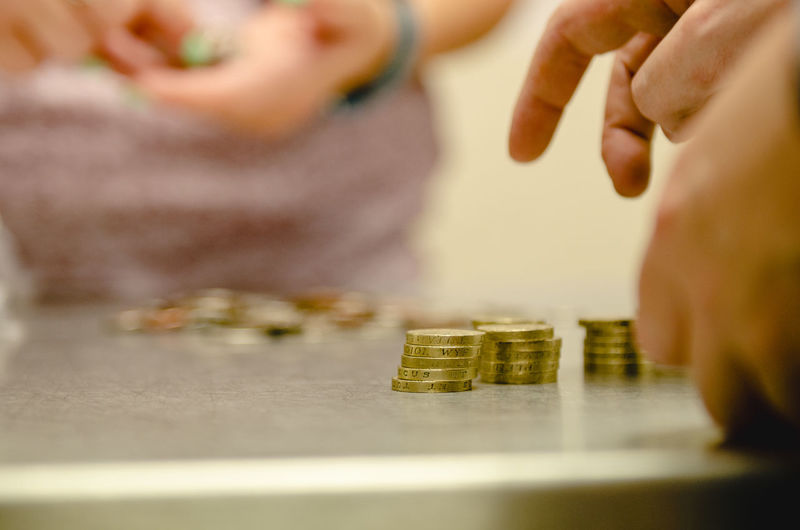 Cropped image of person counting coins on table