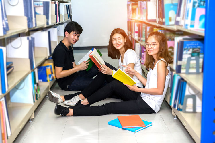High angle portrait of happy friends studying while sitting on floor in library