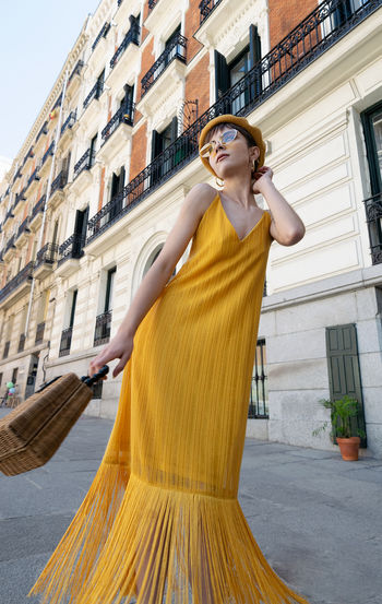 Woman standing against yellow buildings in city
