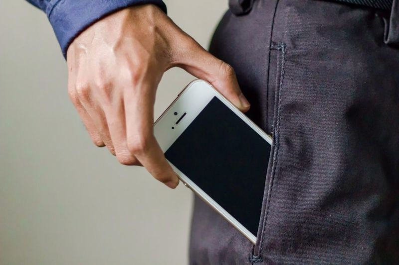 Midsection of man with smart phone in trousers pocket