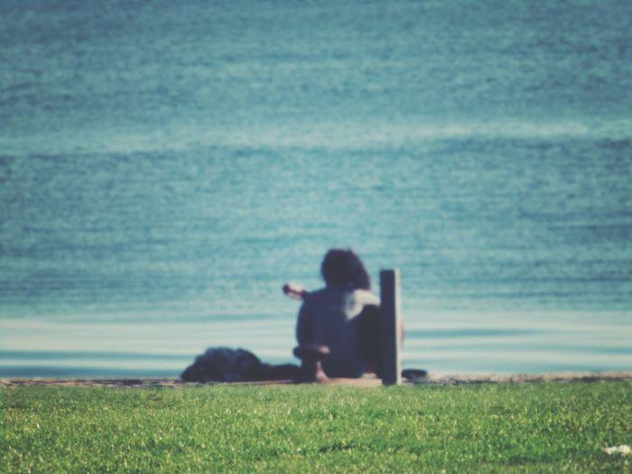 Man sitting on grass by sea