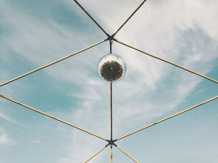 Low angle view of disco ball on metal structure against sky