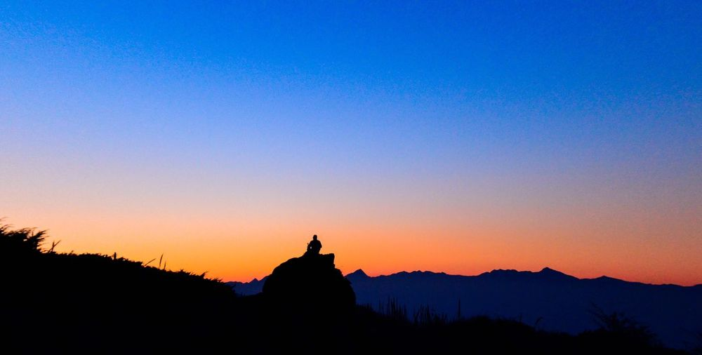 Silhouette statue against clear blue sky during sunset