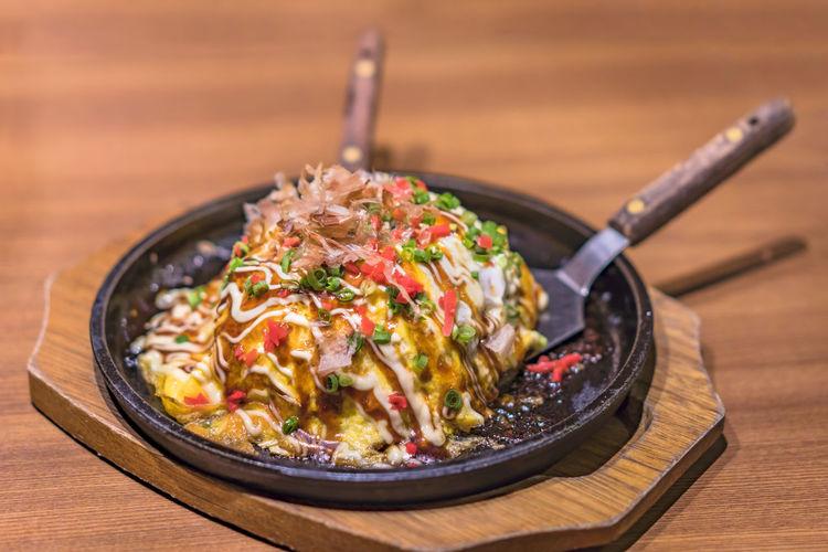 Japanese okonomiyaki covered with katsuobushi leek mayonnaise and bulldog sauce
