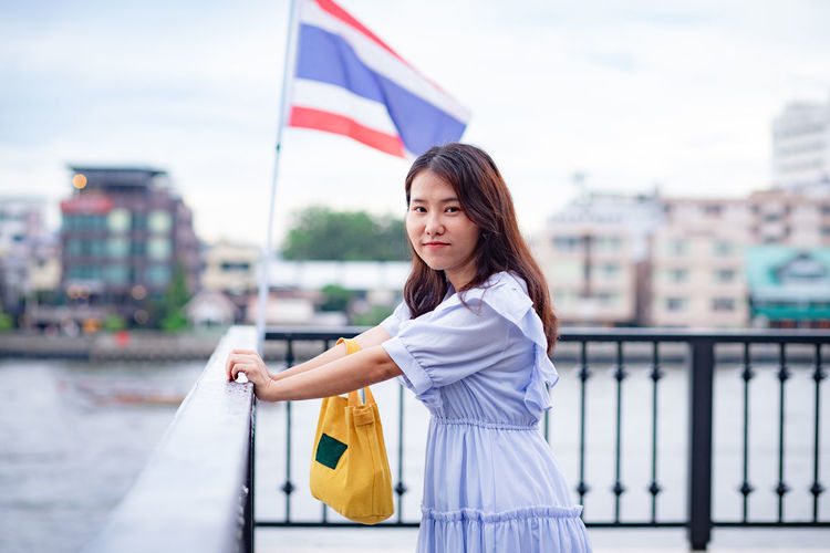 Portrait of woman standing by railing against flag and buildings in city