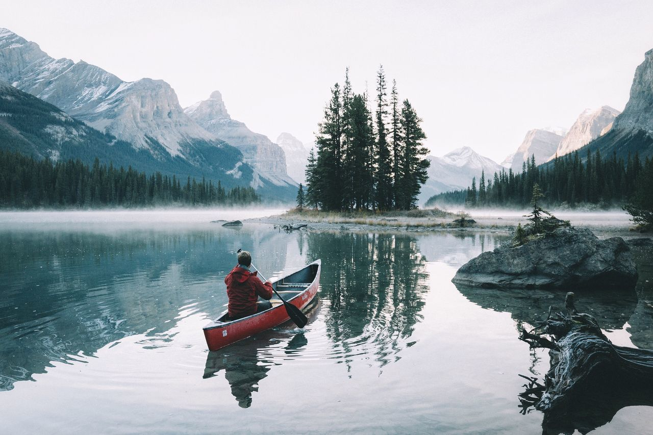 Man Rowing In Canoe In Mountain Lake