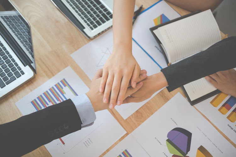 Cropped Image Of Business Colleagues Huddling Hands Over Table In Office