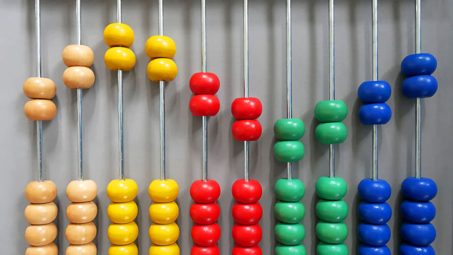 Close-up of multi colored abacus calculator against gray background