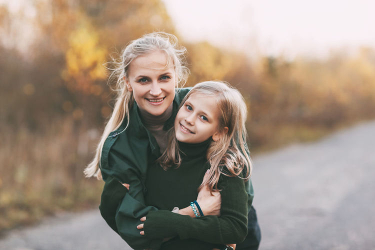 Happy mom and her blonde little daughter hugging and laughing while walking in autumn park