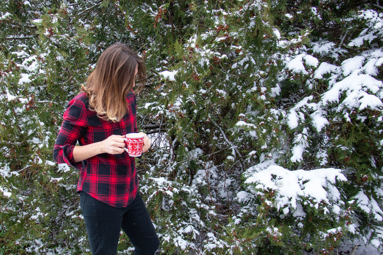 Full length of a woman holding snow covered tree