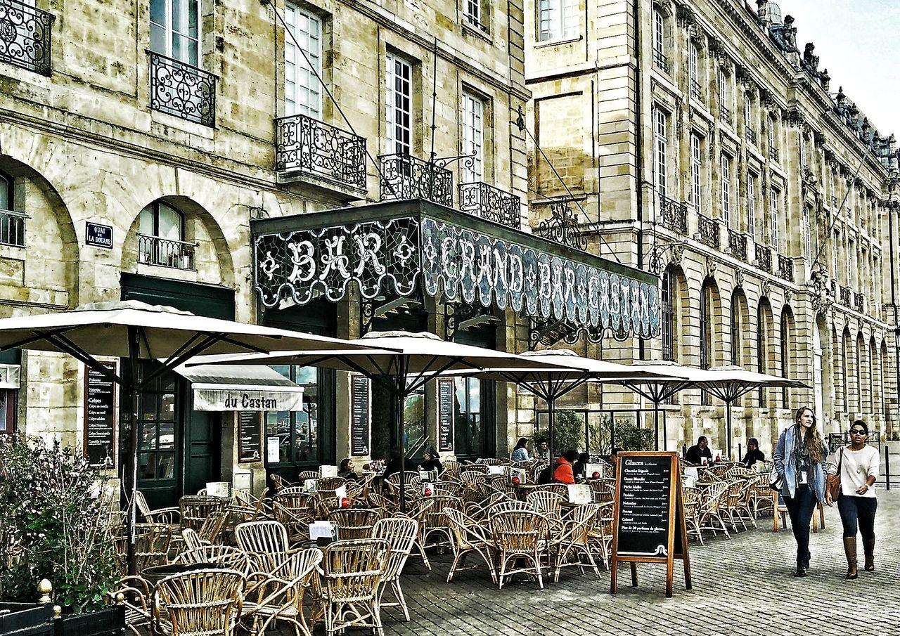 table, chair, architecture, sidewalk cafe, building exterior, restaurant, built structure, cafe, outdoors, city, day, seat, sky, people