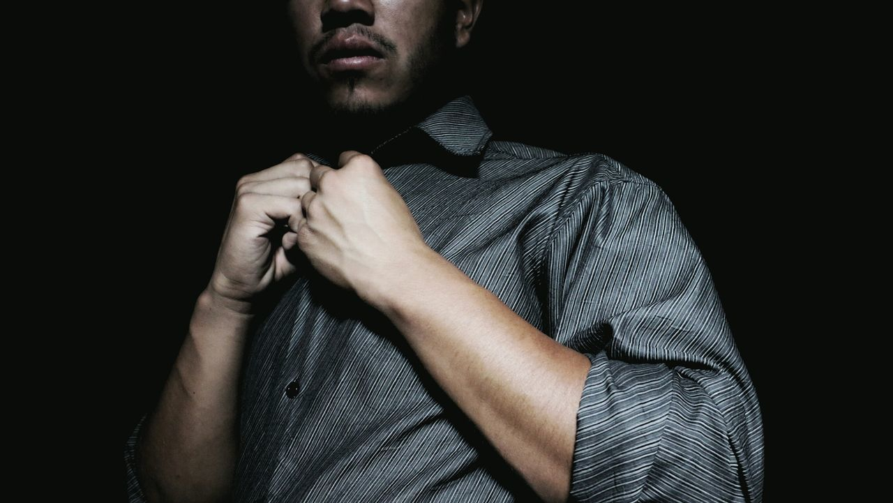 Close-up midsection of man wearing gray shirt against black background