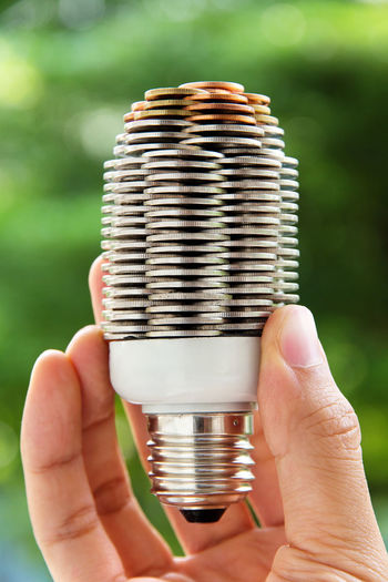 Close-up of hand holding light bulb with stack of coins