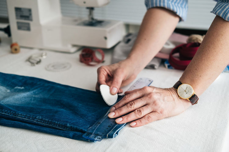 Cropped hands of tailor marking jeans with chalk on table in workshop