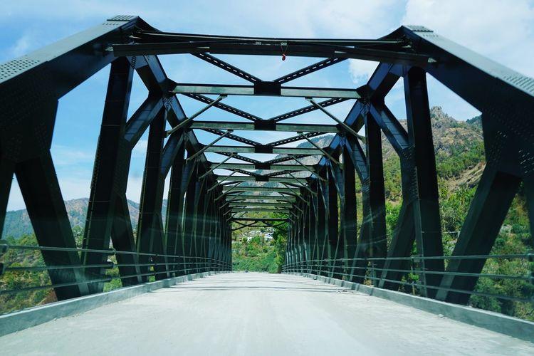 Empty road on bridge against sky