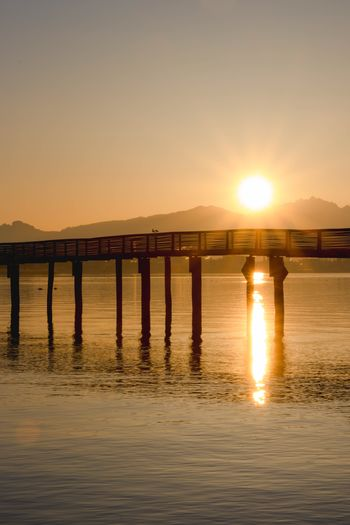Water Sunset Sky Sun Reflection Sea Built Structure Beauty In Nature Architecture Scenics - Nature Silhouette Nature Pier Tranquility Tranquil Scene No People Sunlight Bridge Waterfront Connection