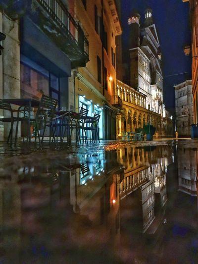 Illuminated restaurant by buildings at night