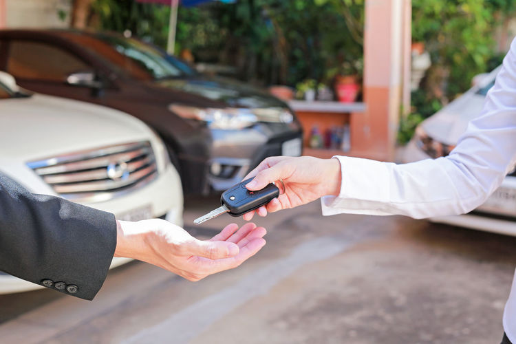 Cropped hand of agent giving car key to owner in city