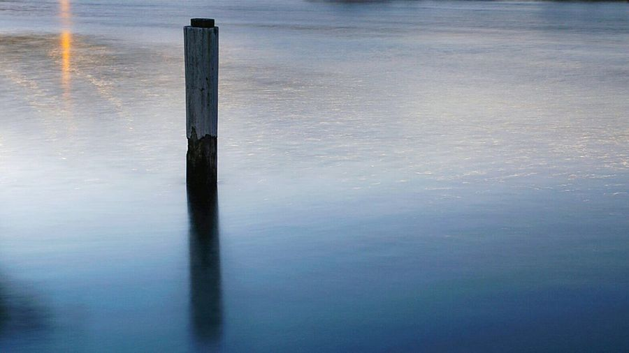 Wooden post in lake during sunset