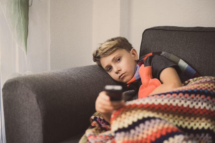 Portrait of ill boy holding remote control while relaxing on sofa at home