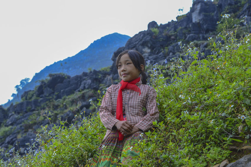 Unidentified young Vietnamese pose for camera with beautiful natural landscape along the Dong Van National Geopark in Ha Giang, Vietnam. Plant Casual Clothing Nature Outdoors One Person Real People Lifestyles Leisure Activity Young Adult Mountain Front View Young Women Standing Day Waist Up Beauty In Nature Land Women Scenics - Nature Beautiful Woman Contemplation