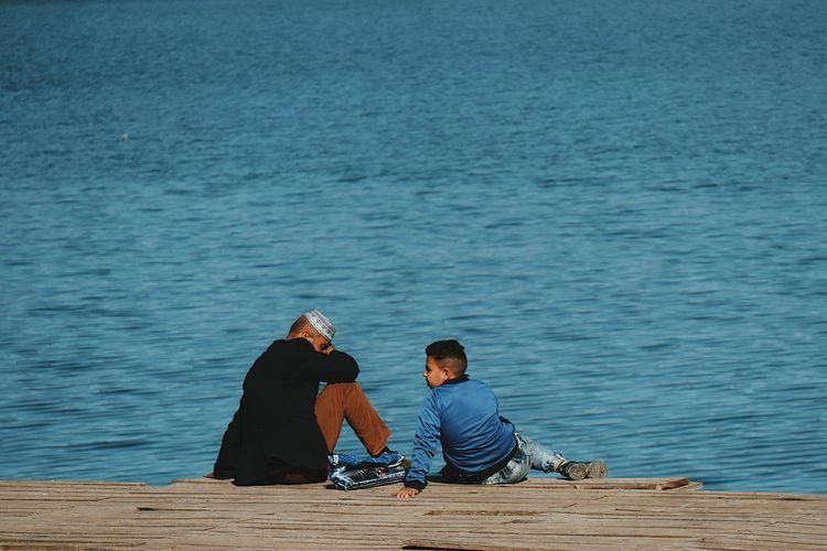 Man and teenage boy sitting against lake