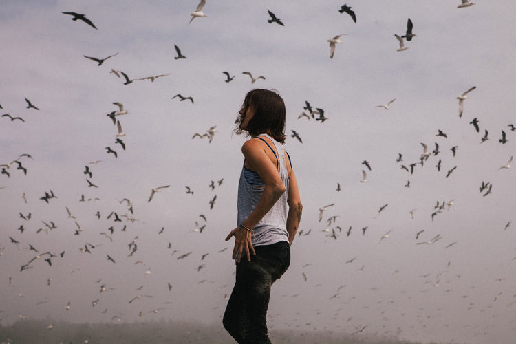 Full length rear view of woman flying birds