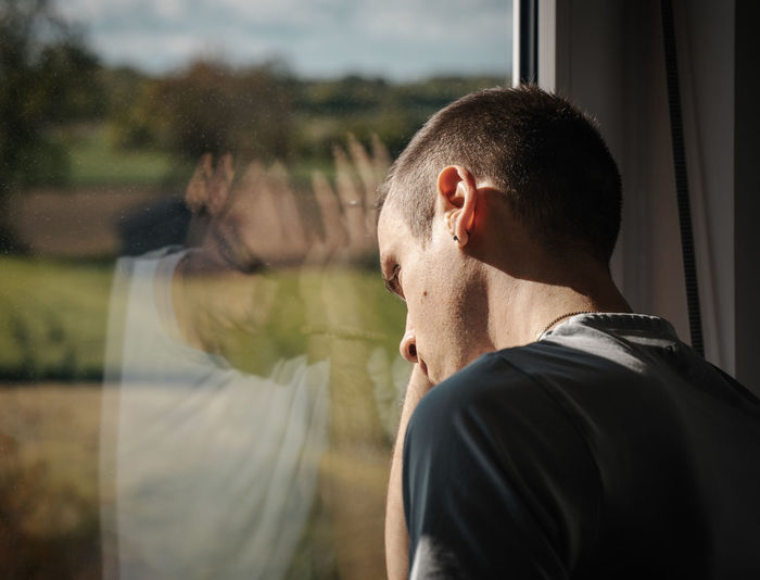 Desperate man stands hopelessly at the window