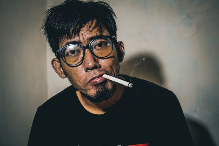 Portrait of man smoking cigarette against wall