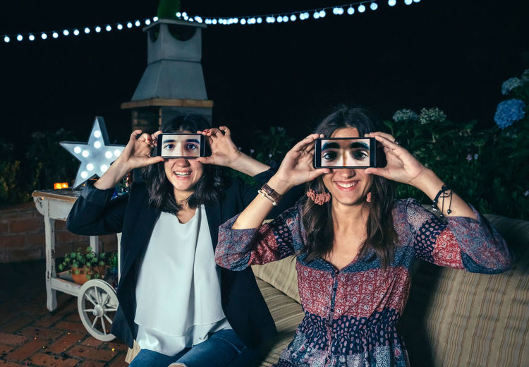 Funny young women holding smartphones showing male eyes in the screen on a outdoors party Celebration Fun Funny Garland Horizontal Screen Sitting Woman Caucasian Covering Display Eyes Female Girl Grimace Male Night Outdoors Party Phone Smartphone Smiling Sofa Togheter Two People