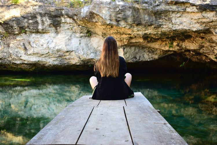 Rear view of woman sitting on pier against cave in sea