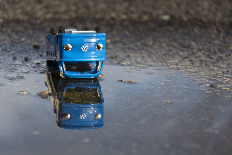 Vintage blue tin toy car with Volkswagen logo lying in a puddle Blue Reflection No People Water Day Outdoors Close-up Puddle Single Object Wet City Volkswagen Car Emissions Scandal Emission Scandal Motor Vehicle Automotive Copy Space VW Crash Accidents And Disasters Concept Manufacturer Germany