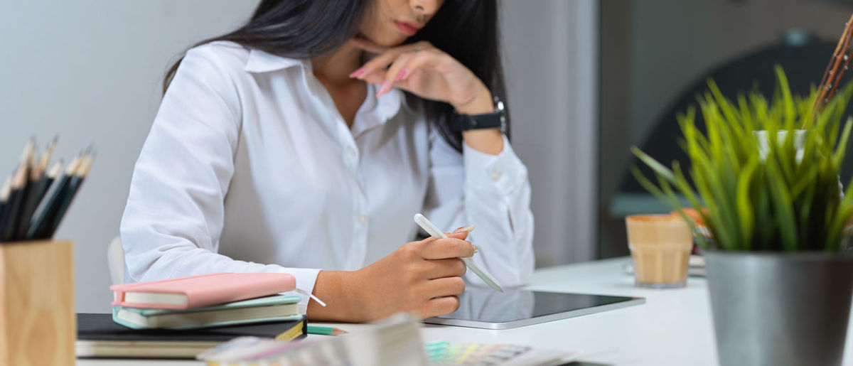 Midsection of woman using digital tablet in office