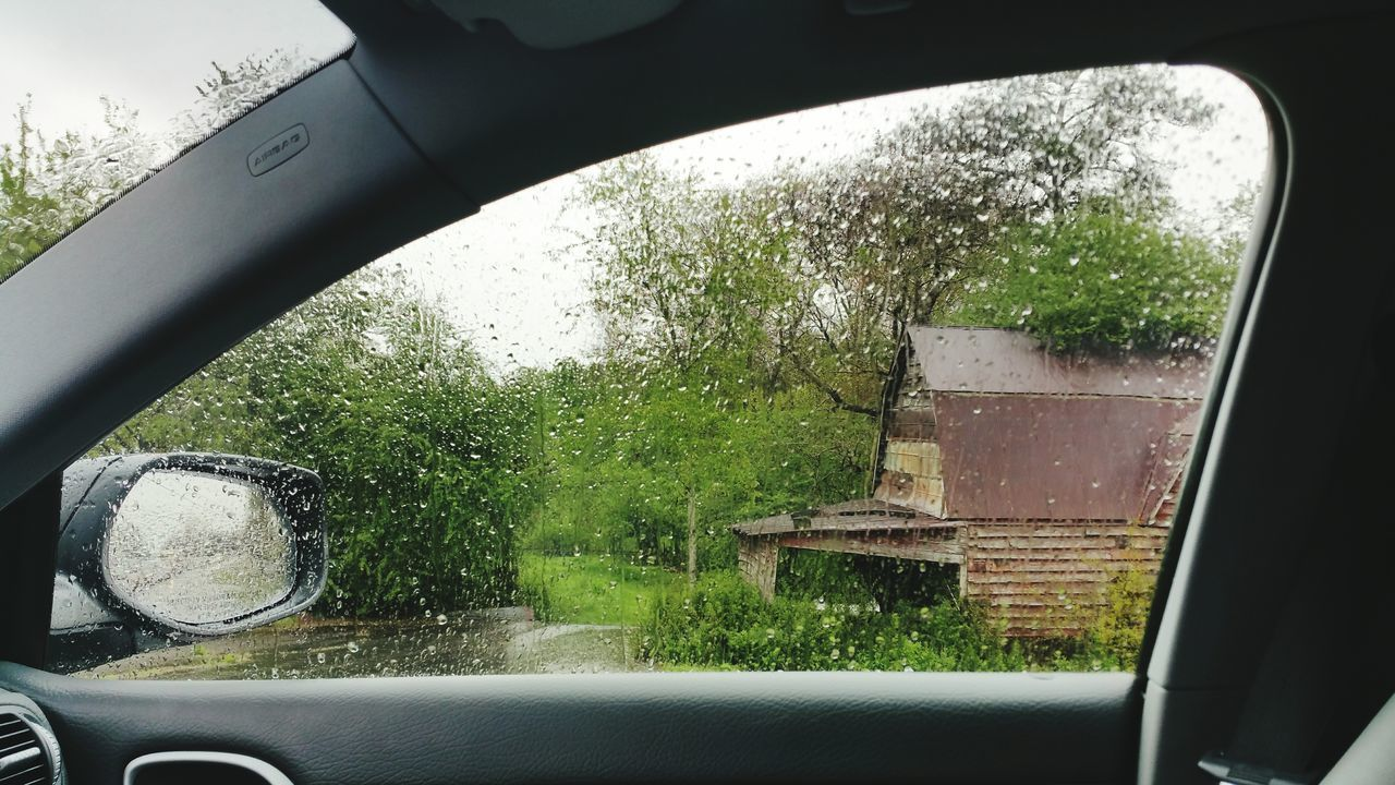 Village House And Green Trees Seen From Wet Car Window