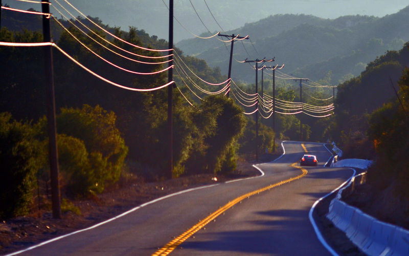 Electric poles by country road against tree mountain