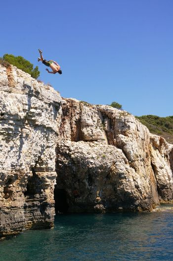 Person jumping in sea against clear sky