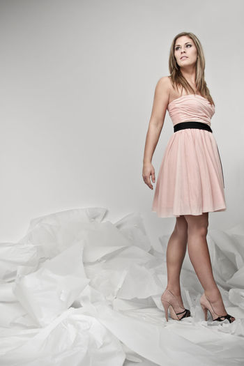 Low angle view of young woman in dress standing against wall