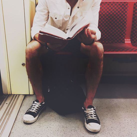 Low section of man sitting on subway train