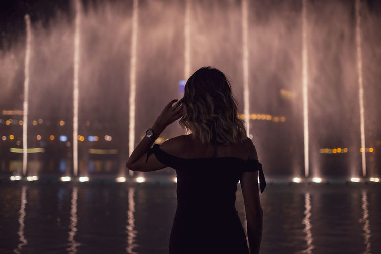 Rear view of woman standing against illuminated fountain in city