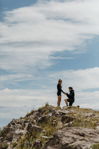 Friends standing on rock against sky